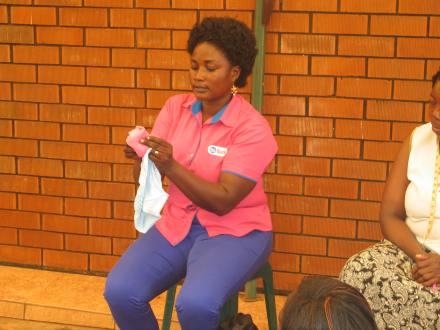 Esther demonstrating to the ladies hoe to use the pads
